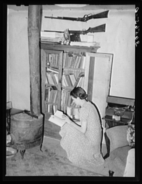 Wife of farmer at her bookcase in her log home. Pie Town, New Mexico