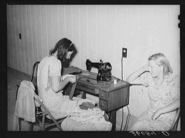 Wife of migratory agricultural laborer sewing at the Aqua Fria migratory labor camp, Arizona. These machines are rented for a nominal sum which remains in the camp fund to be used as the camp committee decides