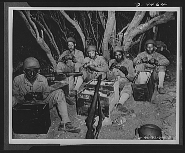 With an airfield security detachment in Hawaii. Constant practice keeps the troops alert at an airfield security post in Hawaii. Shown loading clips at Dusty Hollow Training Center there are, left to right: Private Moses Riley, Eastontown, Georgia; Private Lee Bullock, New York City; Private First Class Mathew Riley, Logton, Mississippi; Private Ulis Pickett, Albeeville, Alabama and Private Mack Underwood, Bessemer, Alabama