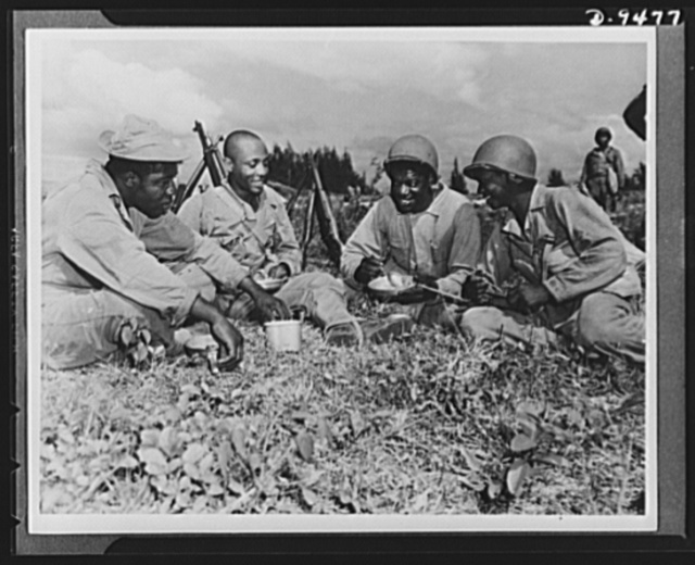 With an airfield security detachment in Hawaii. Constantly on maneuvers in Hawaii, members of an airfield security detachment enjoy chow in the field. Shown left to right are: Corporal John L. Sellers, Columbus, Georgia; Private Joseph English, Greensboro, Georgia; Private Bennie W. Samuel, Albany, New York, and Private John Preston, Tampa, Florida