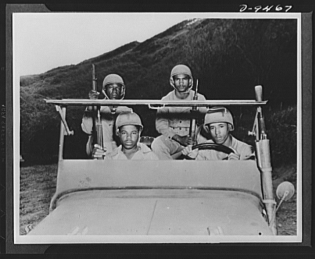 With an airfield security detachment in Hawaii. Four men in a jeep at the Dusty Hollow Training Center included the following members of an airfield security detachment in Hawaii. Front seat (left to right): Private Lester H. Howell, Statesville, North Carolina and Private First Class Thomas Irvin, North Ashville, Tennessee. And rear: Private Arthur W. Blakemore, Saint Louis, Missouri and Private First Class Donald Wilson, Sanford, Florida