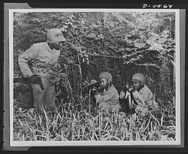 With an airfield security detachment in Hawaii. Kneeling and firing from cover is practiced regularly by an airfield security detachment at Dusty Hollow Training Center in Hawaii. Shown left to right are: Private Robert L. Rogers, Abbeville, Georgia; Private Harry Frank Anniston, Alabama