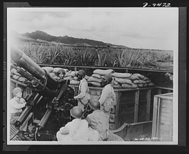 With an airfield security detachment in Hawaii. Operating anti-aircraft machinery in a dugout with an airfeild security detachment in Hawaii are (left to right): Corporal Harvey Jones, New York City; Private Samuel Moffitt, Siler City, North Carolina; Private Jay G. Pappy, New York City; Private First Class James Masfield, New York City; Private Walter Johnson, New York City and Private Walter Phillips, New York City