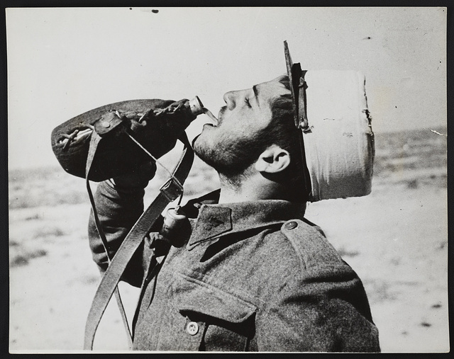 """With the free French forces in the Western Desert: A """"poilu"""" taking a drink after dinner"""