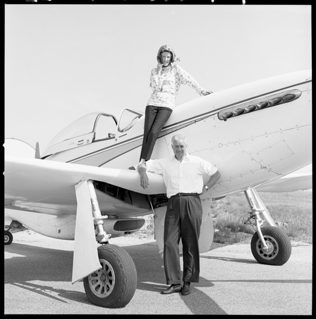 [Woman standing on wing of small airplane, man standing next to airplane]