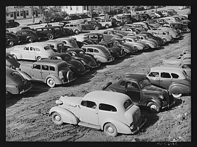 Workers' automobiles parked near the airplane factories. San Diego, California. Providing parking space for automobiles and getting the cars in and out at shift changing time have been big problems