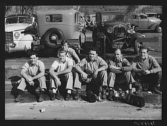 Workers eating lunch on curb across the street from the Consolidated Airplane Factory. San Diego, California