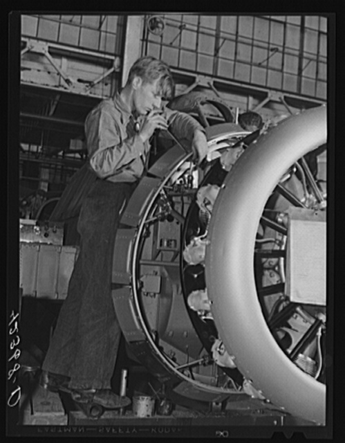 Working on the intricate job of fitting the engine to the fuselage of a plane at The Vought Sikorsky Aircraft Corporation. Stratford, Connecticut