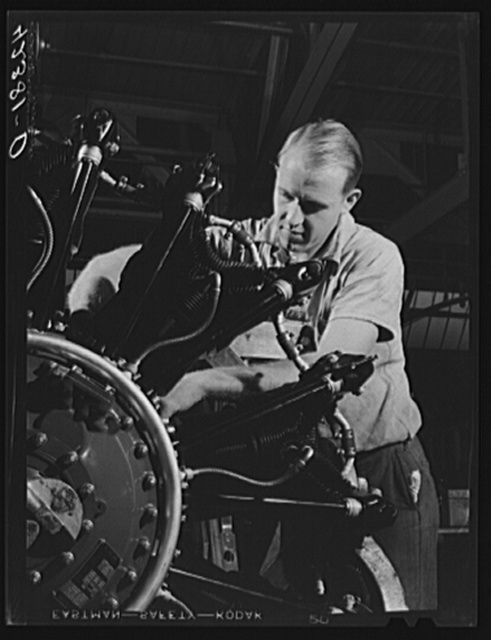 "Workman on the final assembly of a Pratt and Whitney ""WASP"" engine. East Hartford, Connecticut"