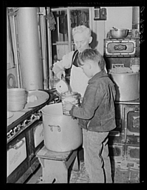 Young boy receiving pail of soup in kitchen of city mission. Dubuque, Iowa