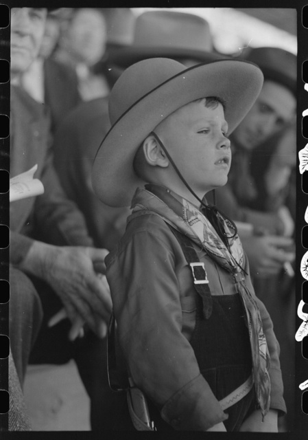 Youngster in cowboy costume watching the rodeo at the San Angelo Fat Stock Show, San Angelo, Texas