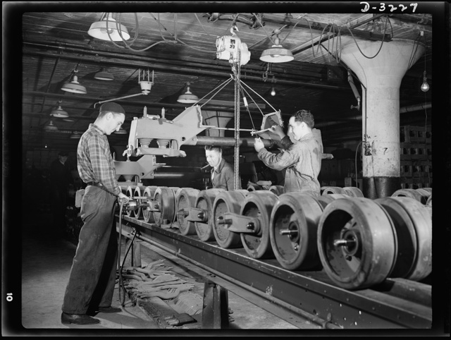 A bogy assembly for an Army halftrac scout car takes shape on the production line of an Ohio truck plant. When it's completed it must be able to stand rigid inspections. White Motor Company, Cleveland, Ohio