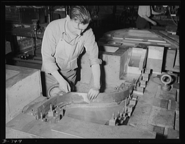 A die maker checking joints of a trim and pierce die which will be used to stamp out parts of automobile fenders. Photo made at Frederick Colman & Sons, Inc., Detroit, Michigan