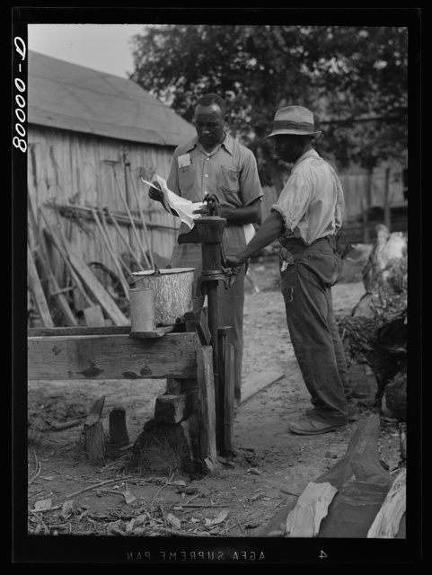 A FSA (Farm Security Administration) supervisor consults a borrower about unsanitary water supply. Safe well demonstration, near La Plata, Maryland. Charles County