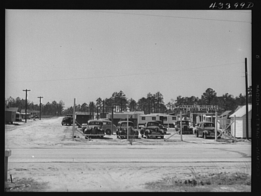 A used car lot adjacent to a trailer settlement of workers from Fort Bragg. Near Fayetteville, North Carolina