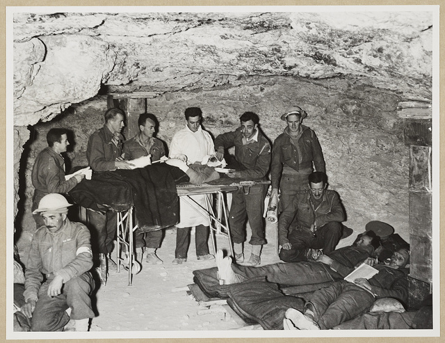 A view inside a S.A. field dressing station which is accommodated in a Bir (well) underground. A patient is shown on the operating table having dressings done to burns, and right are some other patients with an M.O. in attendance. The patients are kept here for several hours under observation and then removed to a base hospital