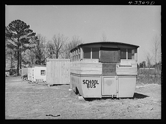 Abandoned school bus occupied by two workers from Fort Bragg, North Carolina in a settlement near the fort