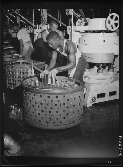 After filling with tomato juice and sealing, metal baskets carrying the cans to chilled water pool for cooling. Phillips Packing Company, Cambridge, Maryland