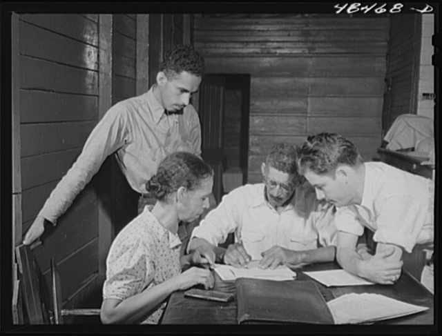Aibonito (vicinity), Puerto Rico. FSA (Farm Security Administration) borrower and his family signing up for another loan. The county supervisor (right) is looking on