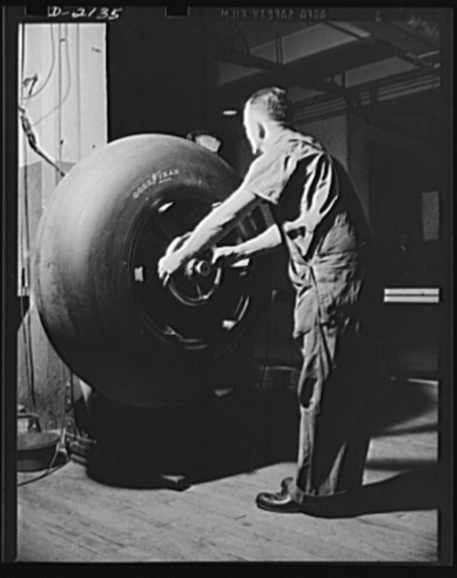 Aircraft tire manufacture. Every airplane tire for military aircraft is carefully balanced on a special machine to guarantee flawless performance in service. Inspector is making final check on airplane tires destined for military service. Goodyear, Akron, Ohio