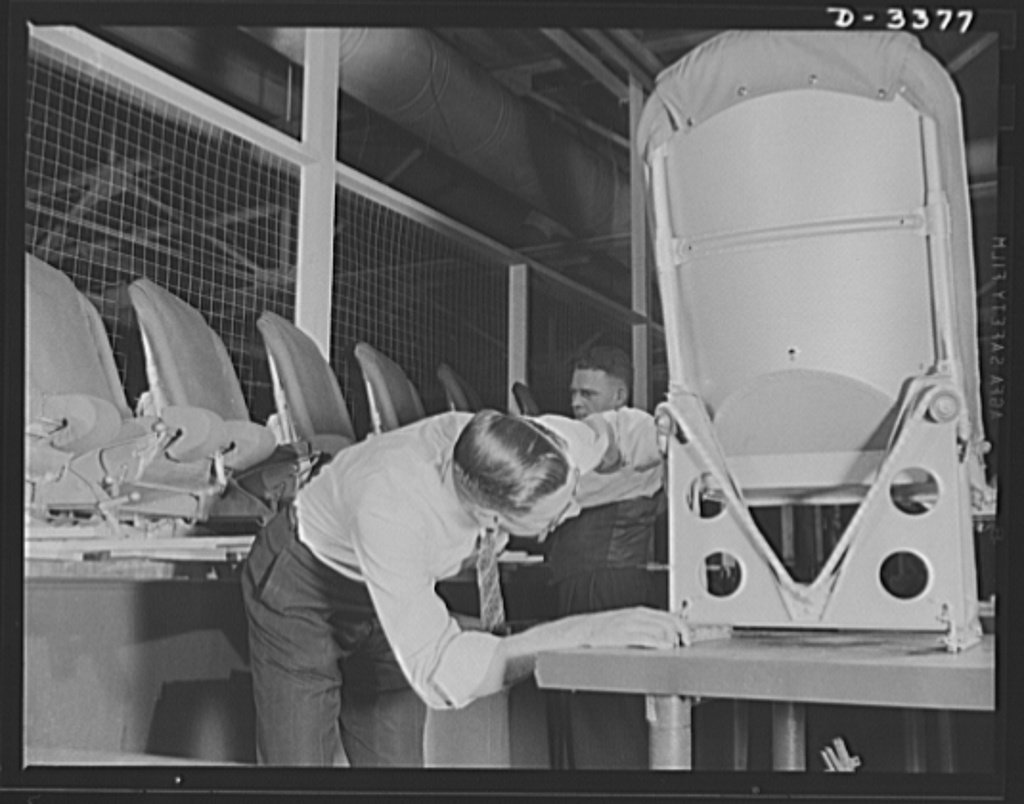 Airplane seat production. Each piece of aluminum necessary to the manufacture of airplane pilot seats must be thoroughly checked before being assembled in this large Midwest rubber factory now converted to war production. Should the precision gauge show up the tiniest imperfection in placement or drilling operations, the stamping will be discarded