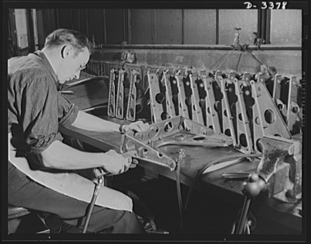 Airplane seat production. Final inspection of completed airplane pilot seats at a large Midwest rubber company converted to war production is a thorough process that must cover every rivet and adjustment. Here inspectors are operating the fore and aft track adjustment which permits the pilot to move his position backward and forward while the plane is in operation