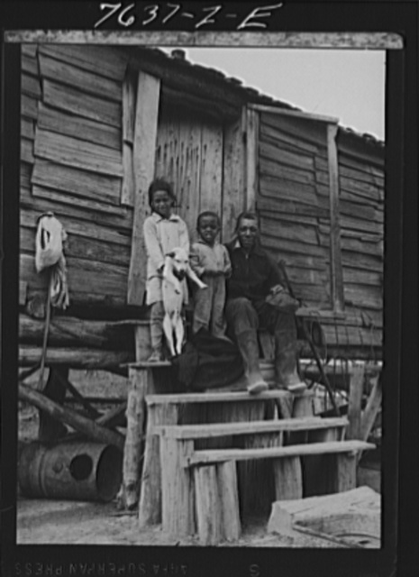 A.J. Hunter, first Negro labor homes occupant, and two of his three children on front steps of shack he vacated. Southeast Missouri