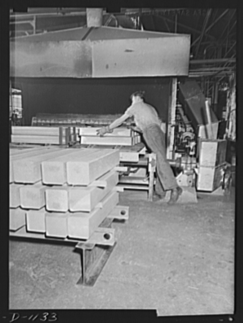 """Aluminum. Reynolds Metal Company, Louisville, Kentucky. """"Strong alloy"""" aluminum ingots, approximately six inches square, are loaded into the heating furnace where they are heated to 800 degree Fahrenheit before rolling operations"""