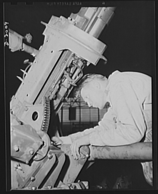 Antiaircraft gun carriage. Assembling the elevating mechanism of a thirty-seven-millimeter antiaircraft gun carriage. This and other control mechanisms of an anti-aircraft gun mounting must operate as easily as your automobile controls so that the gunner may stay trained on his swiftly moving target. War program production scene in a Pennsylvania heavy industry plant. AETNA. Ellwood CIty, Pennsylvania