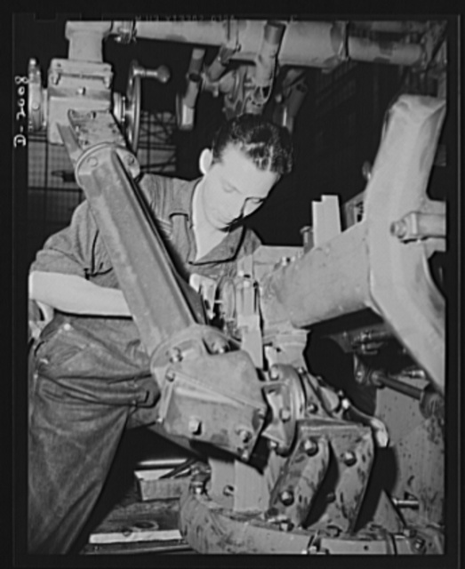 Antiaircraft gun carriage. Assembling the foot firing mechanism on a thirty-seven-millimeter antiaircraft gun carriage. The gunner requires both hands to follow his swiftly moving target, and must get in as many shots as he can while the target is still within range. War program production scene in a Pennsylvania heavy industry plant. AETNA. Ellwood CIty, Pennsylvania