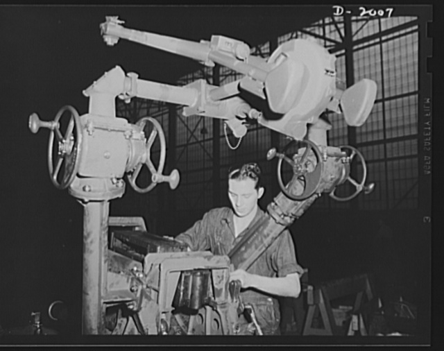 Antiaircraft gun carriage. The elevating mechanism is assembled on a thirty-seven-millimeter antiaircraft gun carriage nearing completion. Care and precision is the watchword in the assembling of these mechanisms. A 300-mile-per-hour target requires a precision instrument to allow the gunner to stay with it. War program production scene in one of Pennsylvania's heavy industry plants now converted to the production of vitally needed military equipment. AETNA. Ellwood City, Pennsylvania