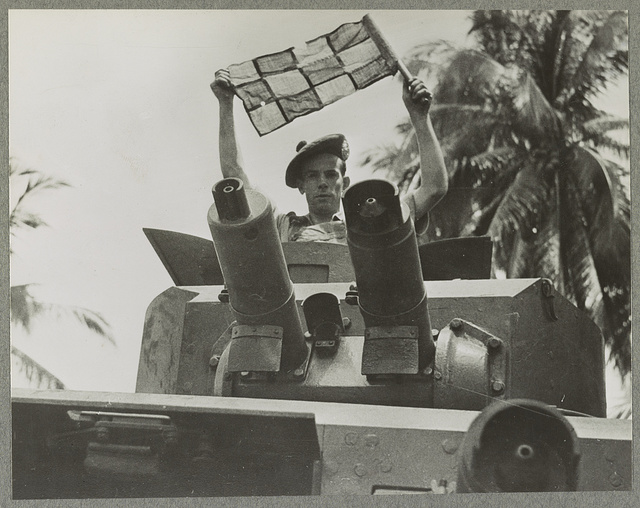 Argylls and Sutherlanders in Malaya Constant practice in patrolling jungle roads keep members of this famous regiment in full fighting trim for their special job. Photo shows a member of a vehicle crew putting up a signal.