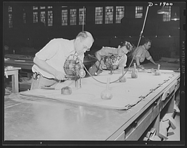 Assault boat Production. Building assault boats for U.S. Marine Corps. After patterns have been laid out, workmen use electric knives to cut through several pieces simultaneously, much in the same manner employed by tailors in mass production unit factory. Goodyear, Akron, Ohio