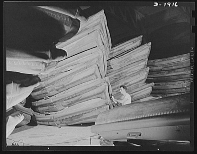 Assault boat Production. Building assault boats for U.S. Marine Corps. Stacks of boats ready for deflation and packing are shown in the balloon room. Goodyear, Akron, Ohio