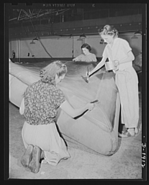 Assault boat Production. Building assault boats for U.S. Marine Corps. Women workers apply preservative waterproof paint to bottom of boat which is nearing completion. Goodyear, Akron, Ohio