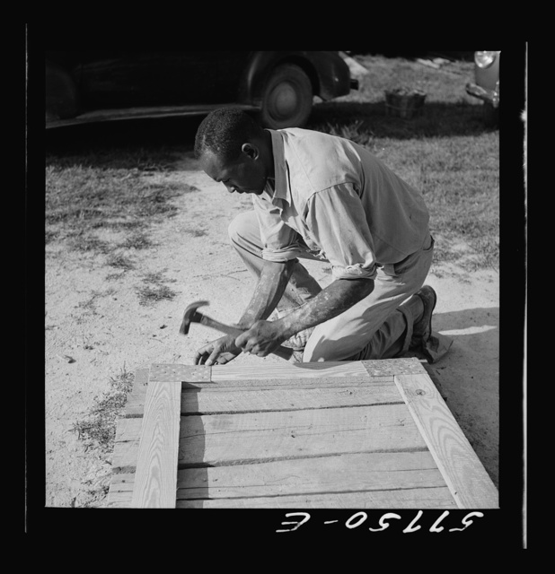 Assembling a joint of screen door. Screen door stock used is one inch by four inches.  Joints are cut square and held together with corrugated fasteners. Screening demonstration. Saint Mary's County, Ridge, Maryland