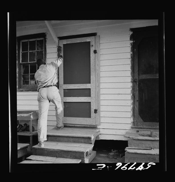 Assembling screen door to door frame. Screening demonstration. Saint Mary's County, Ridge, Maryland
