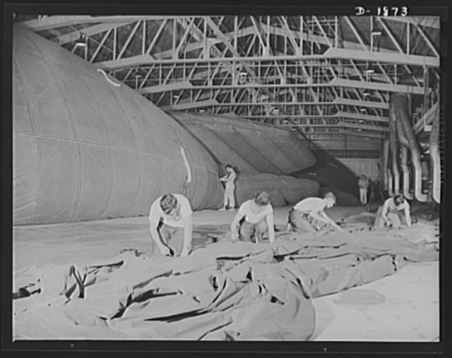 Barrage balloon manufacture. Assembling the balloon. These workers are ready to fasten one-half of a barrage balloon to the other half--the final major step in the assembly of the huge balloon. After this is done, all accessories, ropes and rigging will have to be added before the balloon can be tested, finally inspected, packed and shipped to Uncle Sam. General Tire and Rubber Company, Akron, Ohio
