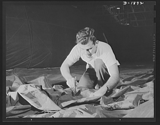 Barrage balloon manufacture. Cementing with a paint brush. This worker is a fabric cementer busy applying a rigging patch to the side of a new barrage balloon. Although the fabric looks mussed at the moment, it will be stretched tight and smooth when the new piece of fabric is added. Seams are triple protected against leaks, folded over, cement-welded, taped on both sides with overlapping rubber adhesive tape. Such seams will never pull apart under pressure. General Tire and Rubber Company, Akron, Ohio