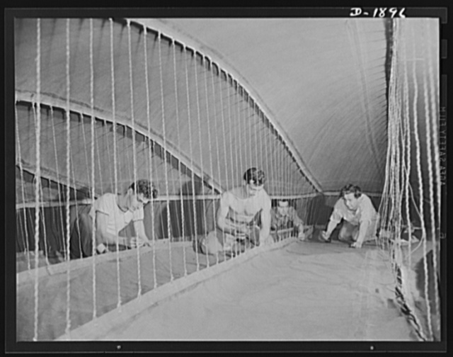 """Barrage balloon manufacture. Fin-shaping cords. These workers are inside the rear-right horizontal fin of a barrage balloon, checking the ropes which give the fin shape and hold it together. Since barrage balloons are non-rigid and entirely collapsible, these ropes come closest to being the """"back-bone"""" for the gigantic """"defenders of cities."""" General Tire and Rubber Company, Akron, Ohio"""
