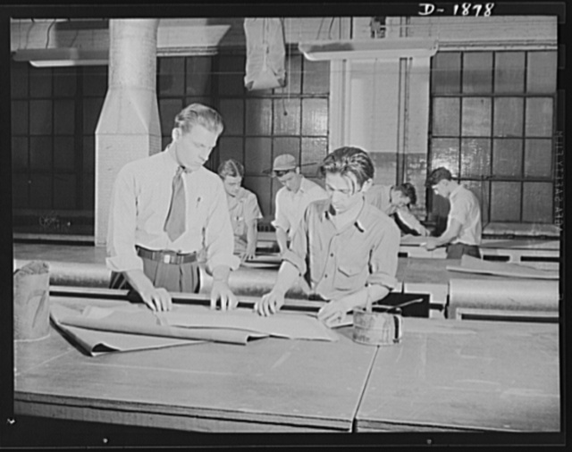 Barrage balloon manufacture. Folding instructions. Supervisor Howard Swires instructs a worker at barrage balloon department in the technique of folding fabric patterns to make efficient use of all working space. General Tire and Rubber Company, Akron, Ohio