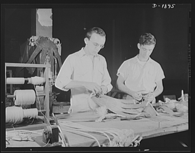 """Barrage balloon manufacture. Handling ropes and fingers. Frayed ropes are attached to the rubberized fabric """"fingers"""" by sewing and cementing to give maximum """"grip"""" on the balloon. Such ropes are fastened to the ground cable which controls the height and flight of the balloon. General Tire and Rubber Company, Akron, Ohio"""