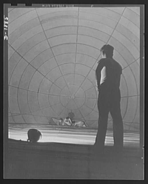 """Barrage balloon manufacture. John and his colleagues. Silhouetted against the spiderweb pattern of the inside of a great barrage balloon, this supervisor watches """"balloon tailors"""" at work on an inside seam. The area in the picture will be filled with helium in service. General Tire and Rubber Company, Akron, Ohio"""