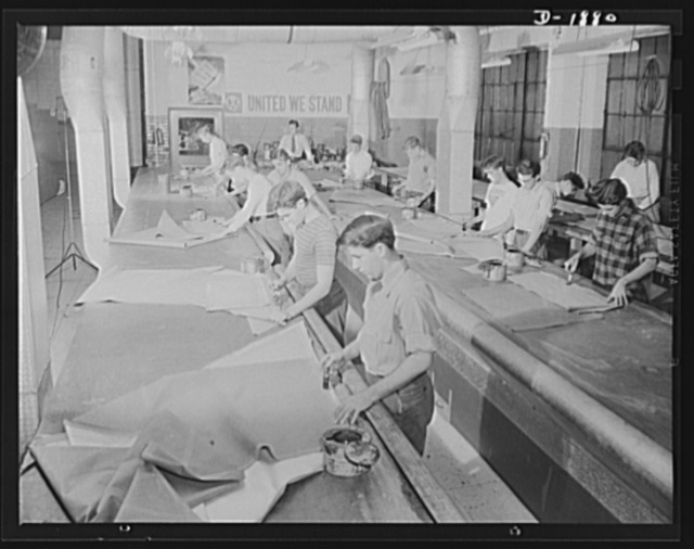 Barrage balloon manufacture. Lineup of cementers. Assembling patterns into gores which in turn are assembled into balloon sections, these workers are charged with making seams strong and gas-tight, since the full tug of gas from the inside, and rigging on the outside is exerted on these sections. General Tire and Rubber Company, Akron, Ohio