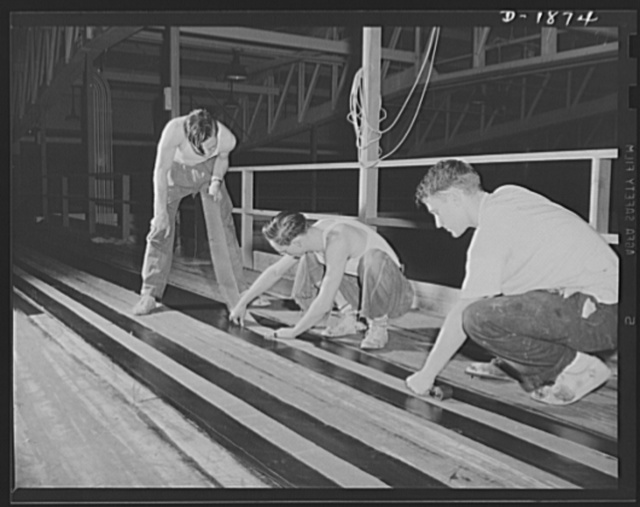 Barrage balloon manufacture. Making a suspension band. These workers are preparing a reinforced band which will be attached longitudinally around the barrage balloon. This band carries most of the rigging by which the balloon is controlled from the ground. General Tire and Rubber Company, Akron, Ohio