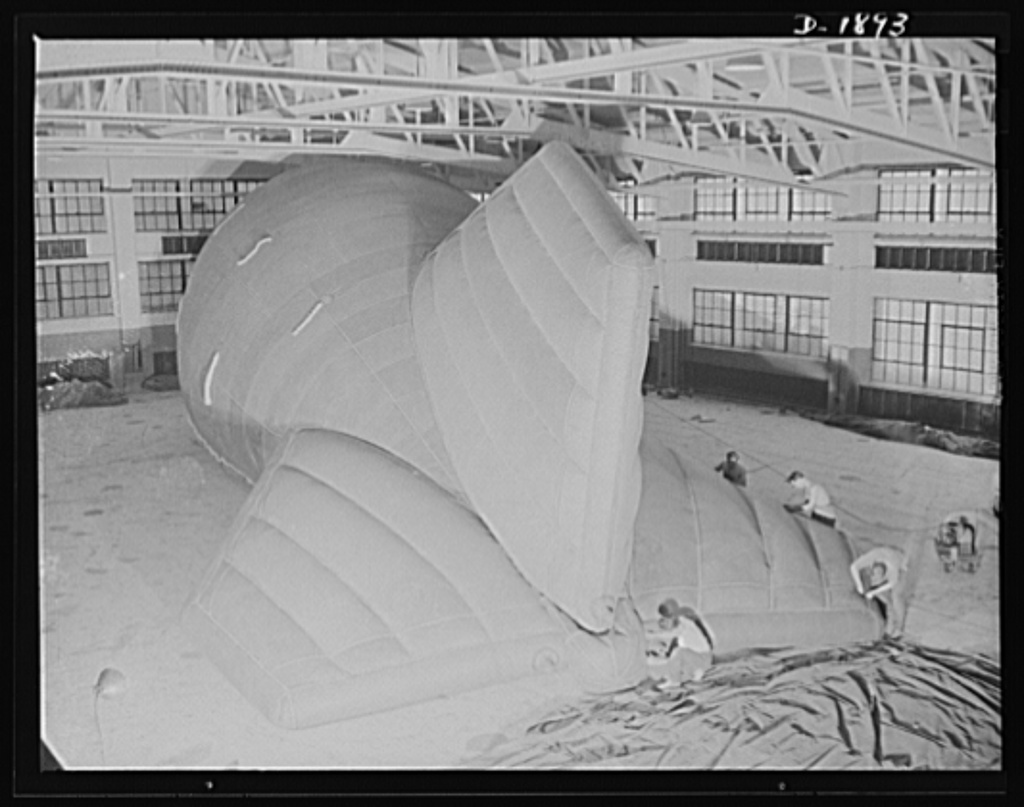 Barrage balloon manufacture. Reinforcing tail rigging of a new ballonet type barrage balloon, these workers at the barrage plant are cementing, seaming and rolling reinforcing tape across points in the tail and fins where strain is greatest. General Tire and Rubber Company, Akron, Ohio