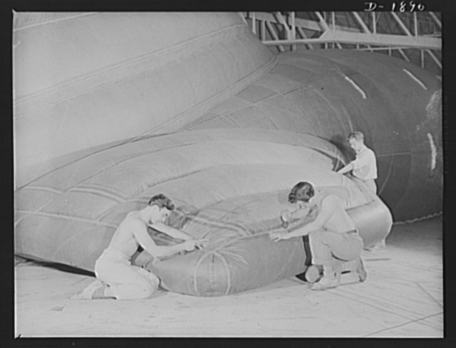 Barrage balloon manufacture. Reinforcing the fins of a fish-of-the-air. These workers at the barrage balloon division, are putting double reinforcements on the right fin of a completed barrage balloon before it is deflated and sent to army training camps Every seam must be absolutely gas- and air-tight, since the tiniest pinhole would permit valuable amounts of precious helium to escape. General Tire and Rubber Company, Akron, Ohio