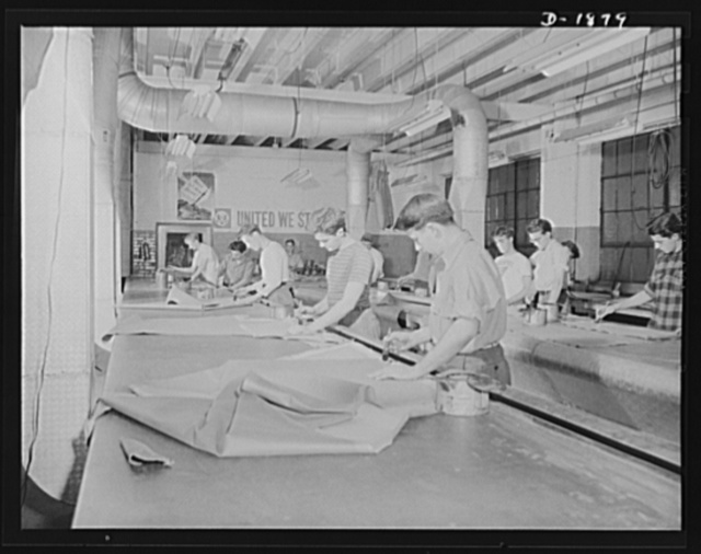 "Barrage balloon manufacture. Seamers at work. Putting rubber cement on both surfaces which are to be fastened together, these workers assemble individual pattern pieces into strips or ""gores"" for barrage balloons being made for army balloon corps. By an ingenious arrangement of folds, strips nearly a hundred feet long can be handled by each worker on the table in front of him. General Tire and Rubber Company, Akron, Ohio"