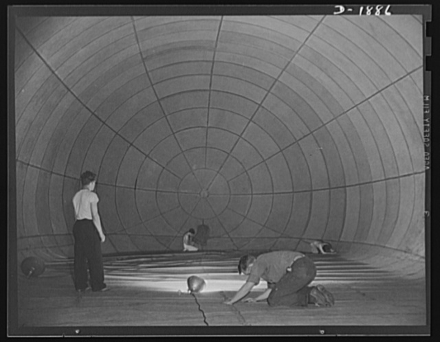 Barrage balloon manufacture. Spider and the flies. Putting last touches on a completed barrage balloon are these workers and their supervisor (standing). To inspect the bag for leaks, the light inside is turned off, leaving the workers in a midnight gloom. Then a co-worker on the outside takes a bright light, and works along the length of the entire balloon, back and forth, until he has covered every inch. The tiniest pinhole shines forth like a bright star in the sky, and these alert inspectors spot it and repair it. Cloth moccasins are worn inside the bag, or else stocking feet--to avoid chafing the fabric. General Tire and Rubber Company, Akron, Ohio