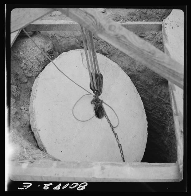 Block and tackle hung from windlass serve as a rig to lower cement cap into place. John Hardesty well project, Charles County, Maryland